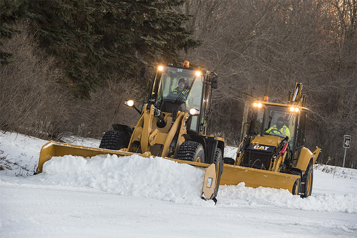 Cat machines - wheel loaders and backhoes - removing snow.